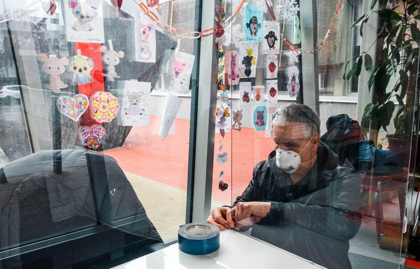 Un travailleur posant des écrans protecteurs à l'école primaire Saint-Romain, afin de limiter les risques de propagation lors du retour des élèves.