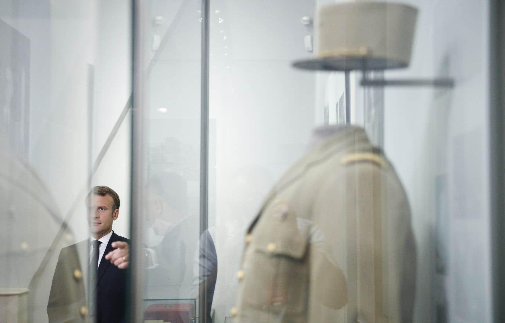 Le président français Emmanuel Macron près de l'uniforme du général de Gaulle exposé lors de la visite du musée de l'Ordre de la Libération.