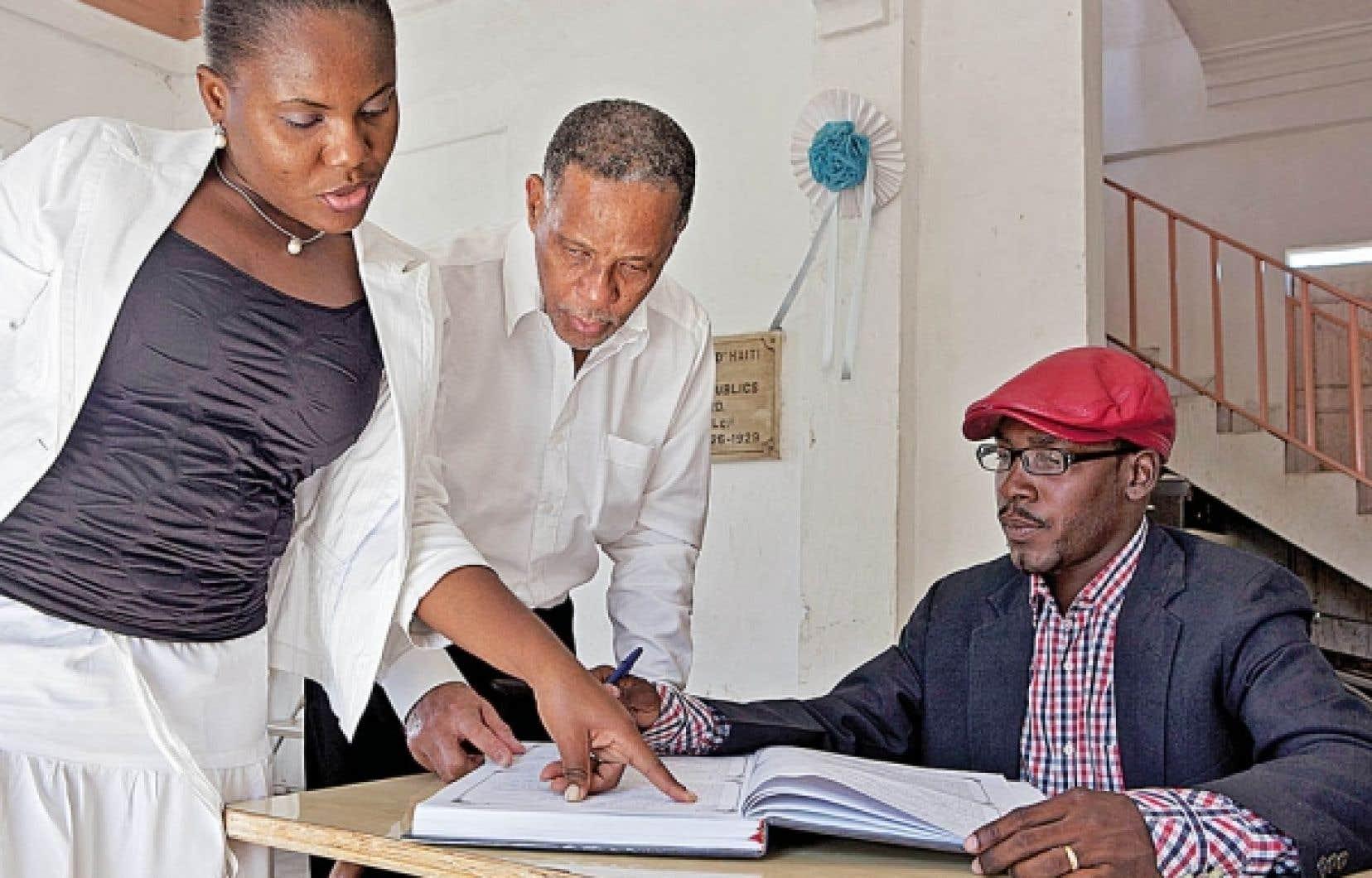 Le secrétaire d'État à l'Intégration des personnes handicapées, Michel Archange Péan, lui-même aveugle, est entouré de son assistante, Guerline Dardignac, et du responsable du registre de la ville de Léogane, Junio Louidor.