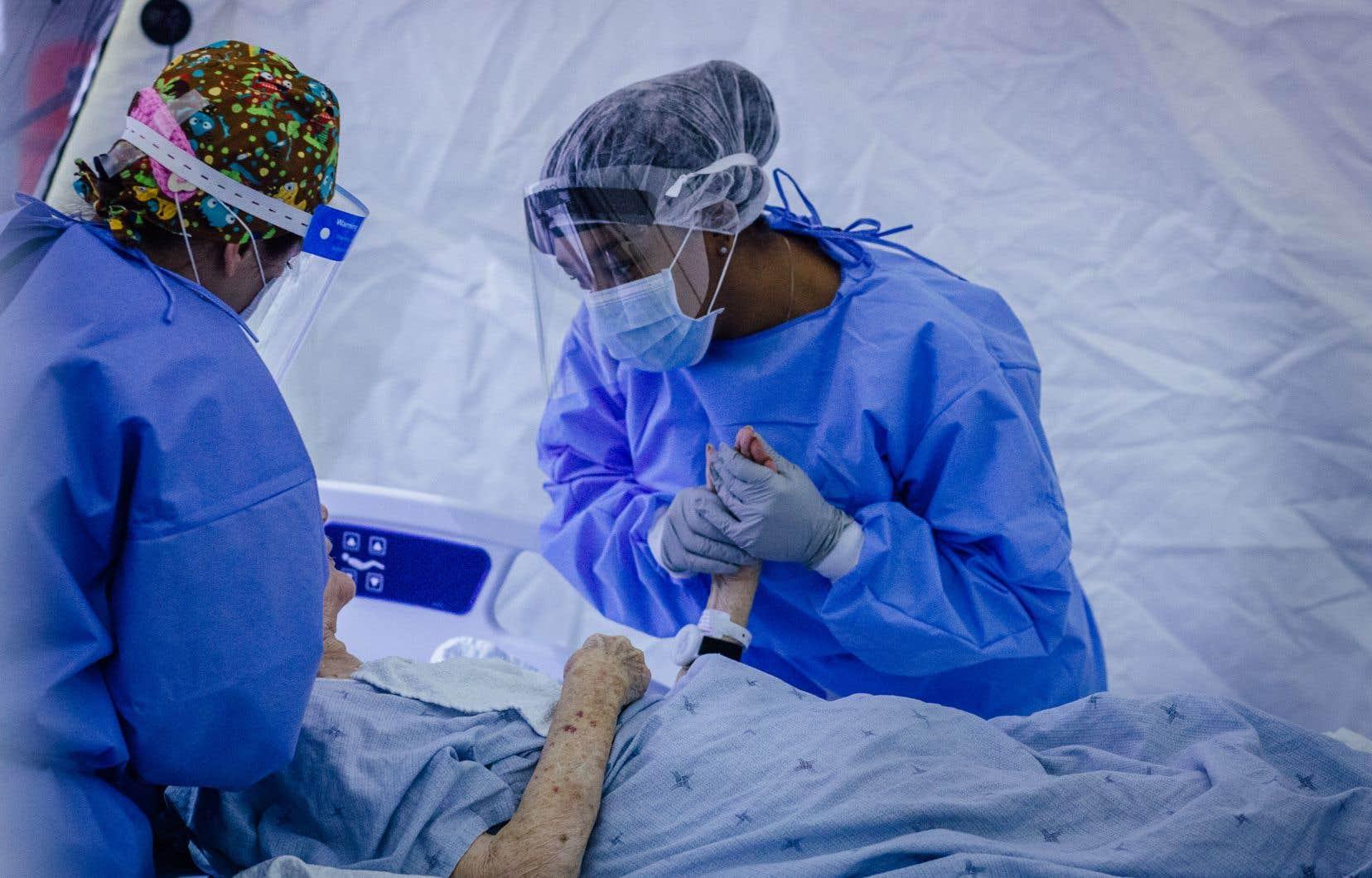 Une infirmière auxiliaire auprès d'une patiente à l'aréna Jacques-Lemaire, à Montréal, qui a été transformé en hôpital.
