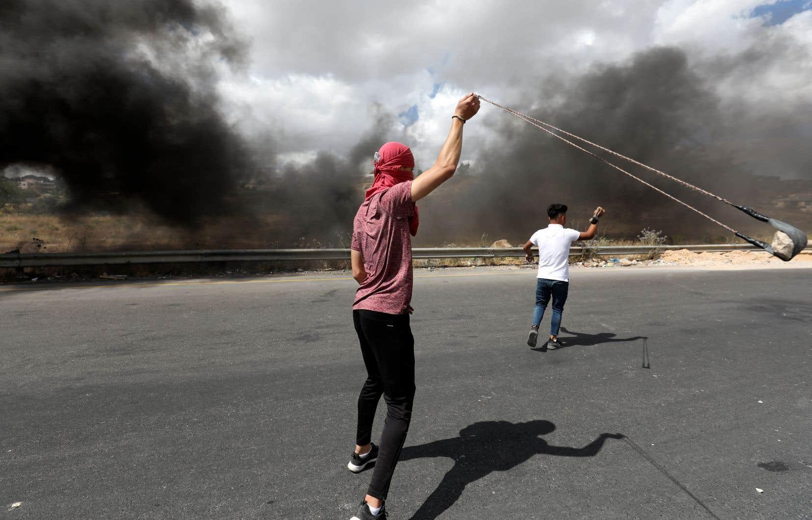 Un militant  palestinien a  fait tournoyer  un lance-pierre devant des  soldats israéliens lors d'une manifestation contre  le projet d'annexion de la  Cisjordanie,  le 19 juin dernier, près  de Ramallah.