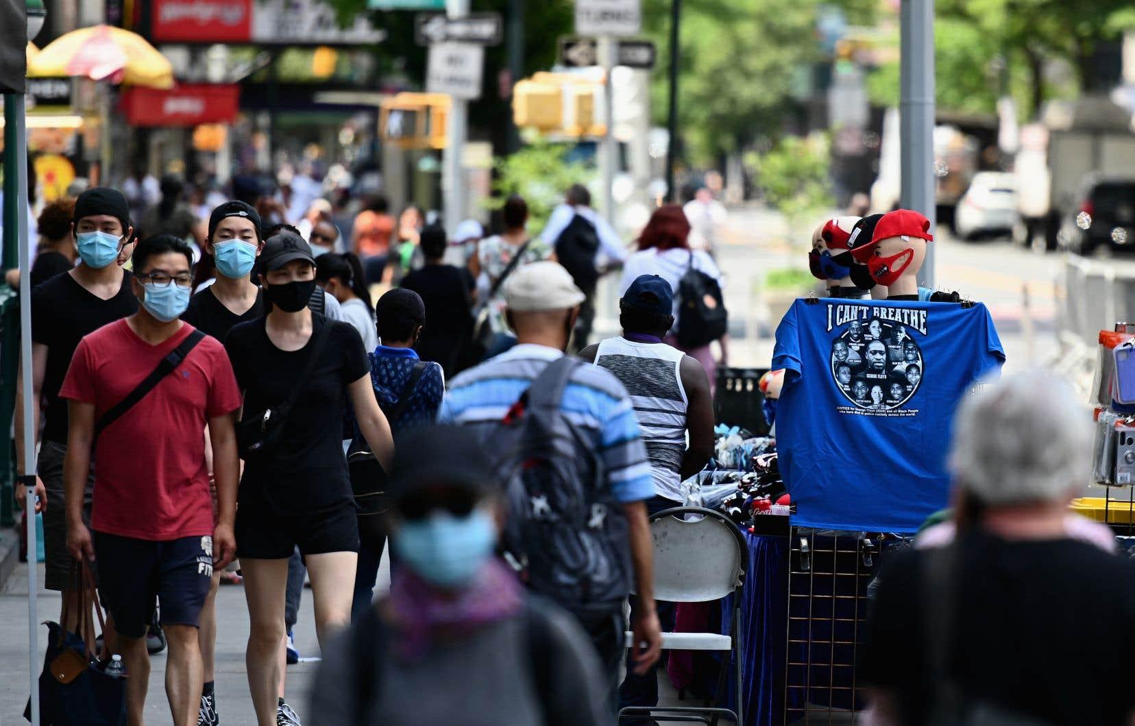 Dans une rue près d'Union Square à New York, jeudi, des piétons portaient des masques pour se rendre dans les commerces qui rouvraient leurs portes après des semaines de fermeture forcée.