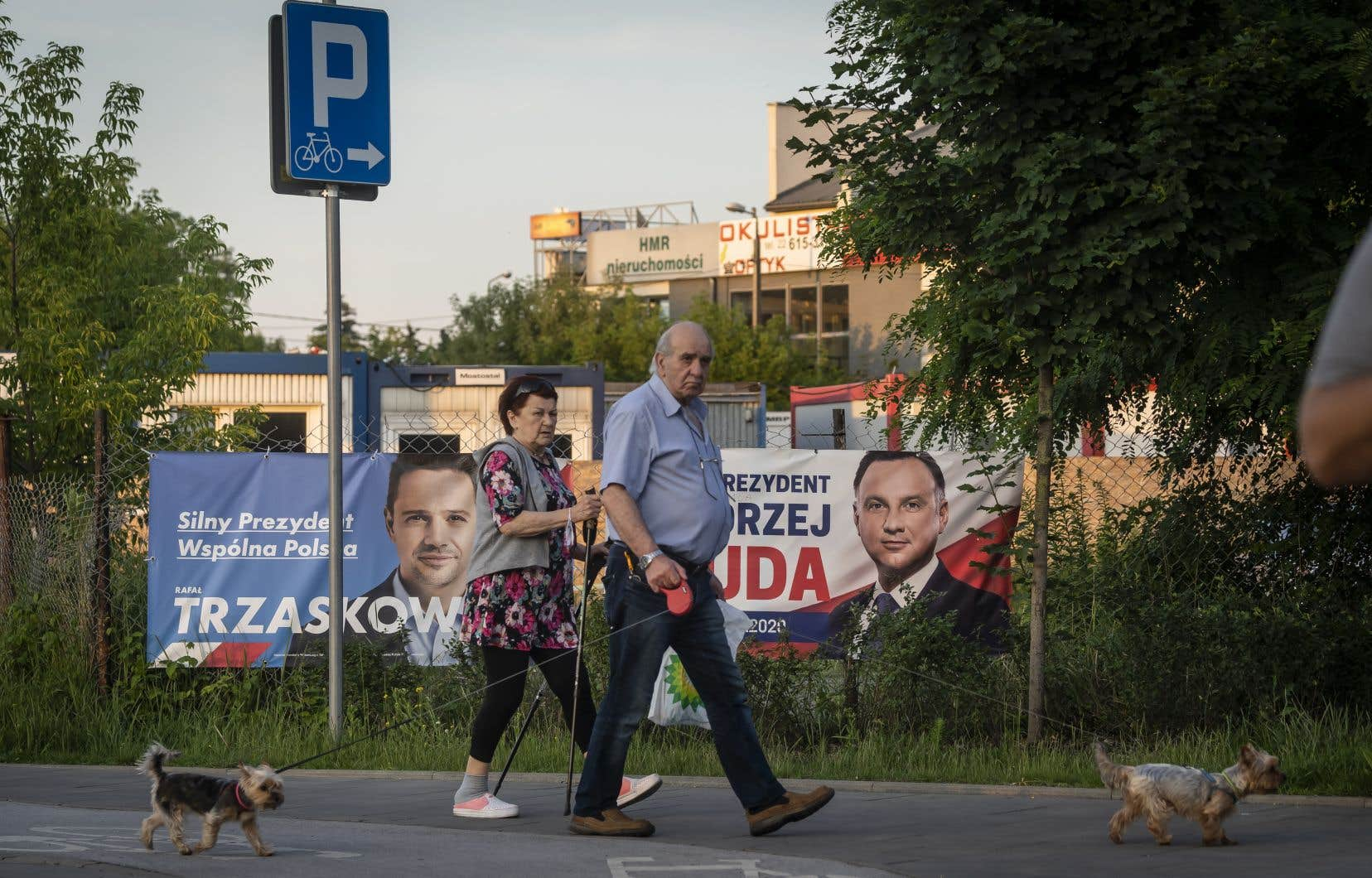 Un couple promenant son chien à Varsovie passe devant les pancartes électorales des deux principaux candidats de l'élection présidentielle polonaise, Rafal Trzaskowski et Andrzej Duda, présentement au coude à coude dans les intentions de vote.