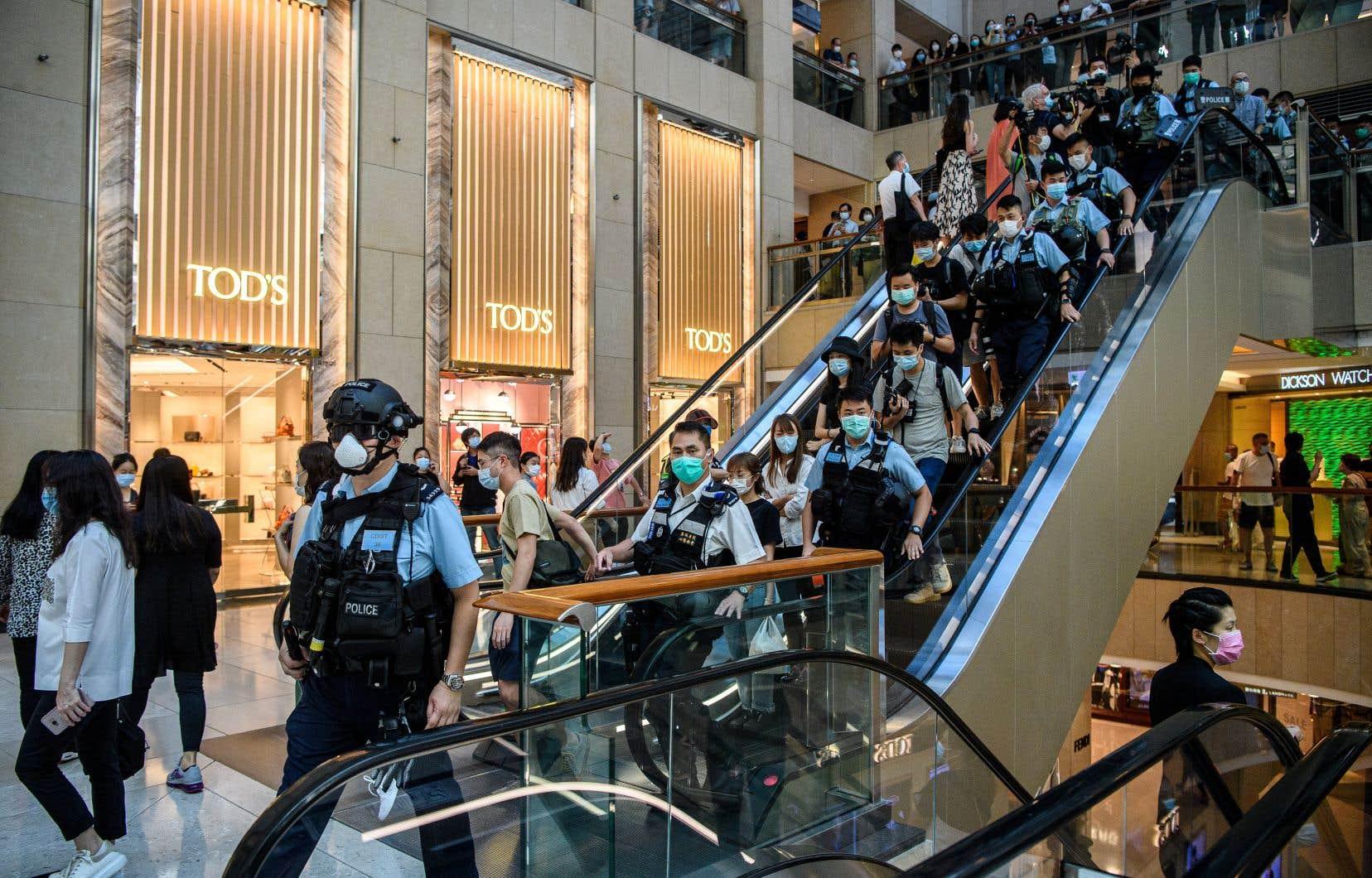 Pour l'opposition hongkongaise et pour plusieurs pays occidentaux, cette loi constitue une attaque contre l'autonomie et les libertés du territoire. Sur la photo, la police entre mardi dans un centre d'achat de Hong Kong pour disperser un rassemblement.