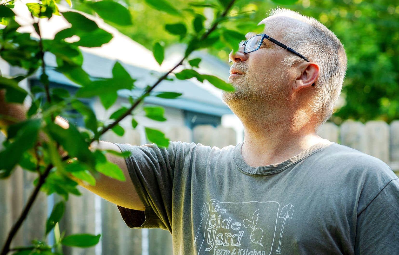 Éric Duchemin dans sa cour arrière, où sa conjointe et lui font pousser fruits et légumes, qui, pour la plupart, seront mis en conserve à l'automne pour éviter le gaspillage.