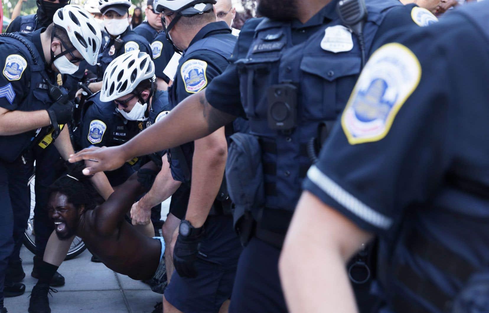 Un homme est arrêté par des policiers en marge d'une manifestation contre le racisme à Washington, samedi.