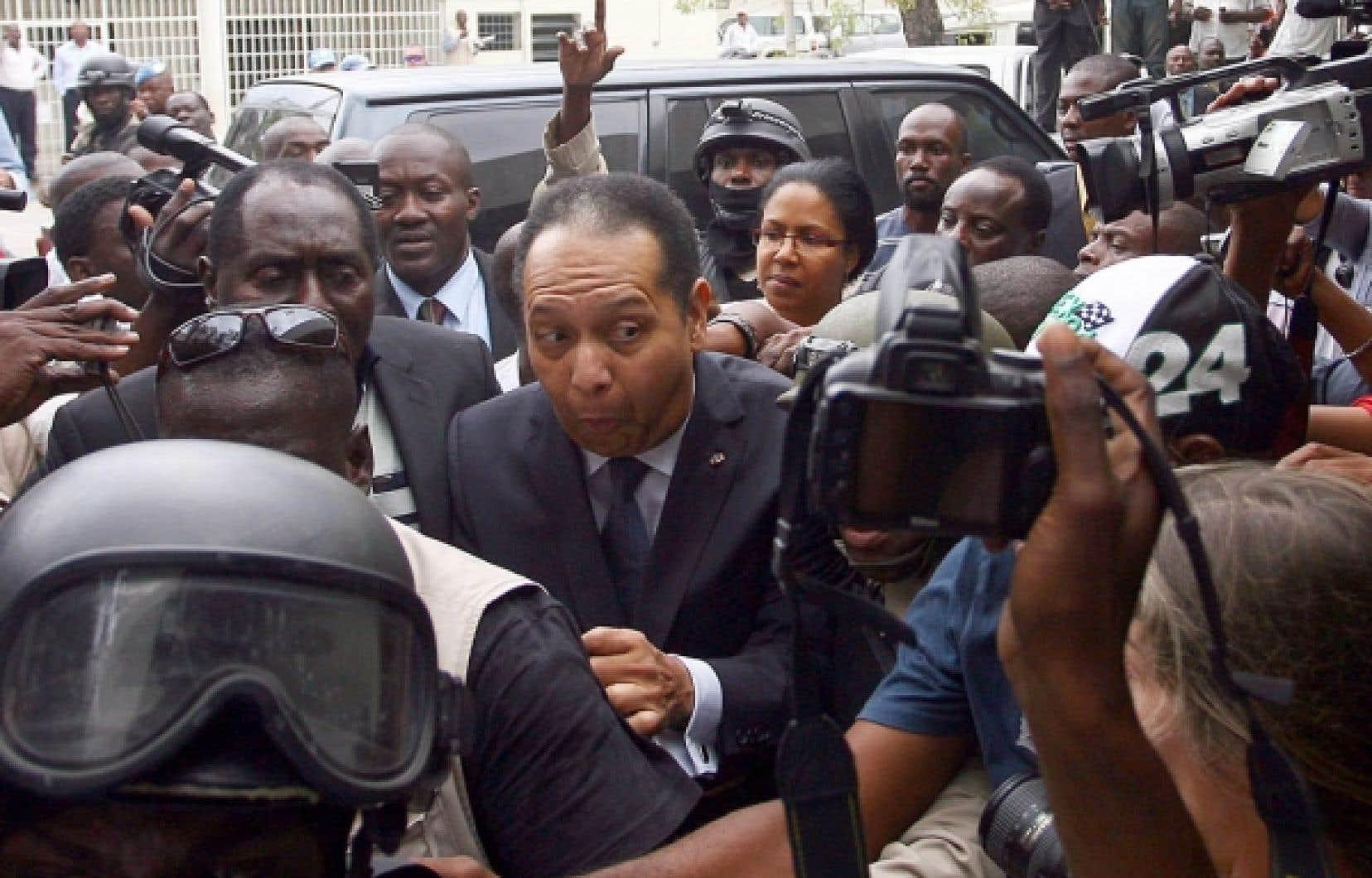 Jean-Claude Duvalier entouré de policiers, de gardes du corps et journalistes lors de son arrivée au parquet de Port-au-Prince, hier. Son cas est maintenant entre les mains d'un juge d'instruction. En attendant, l'ancien dictateur est libre.<br />