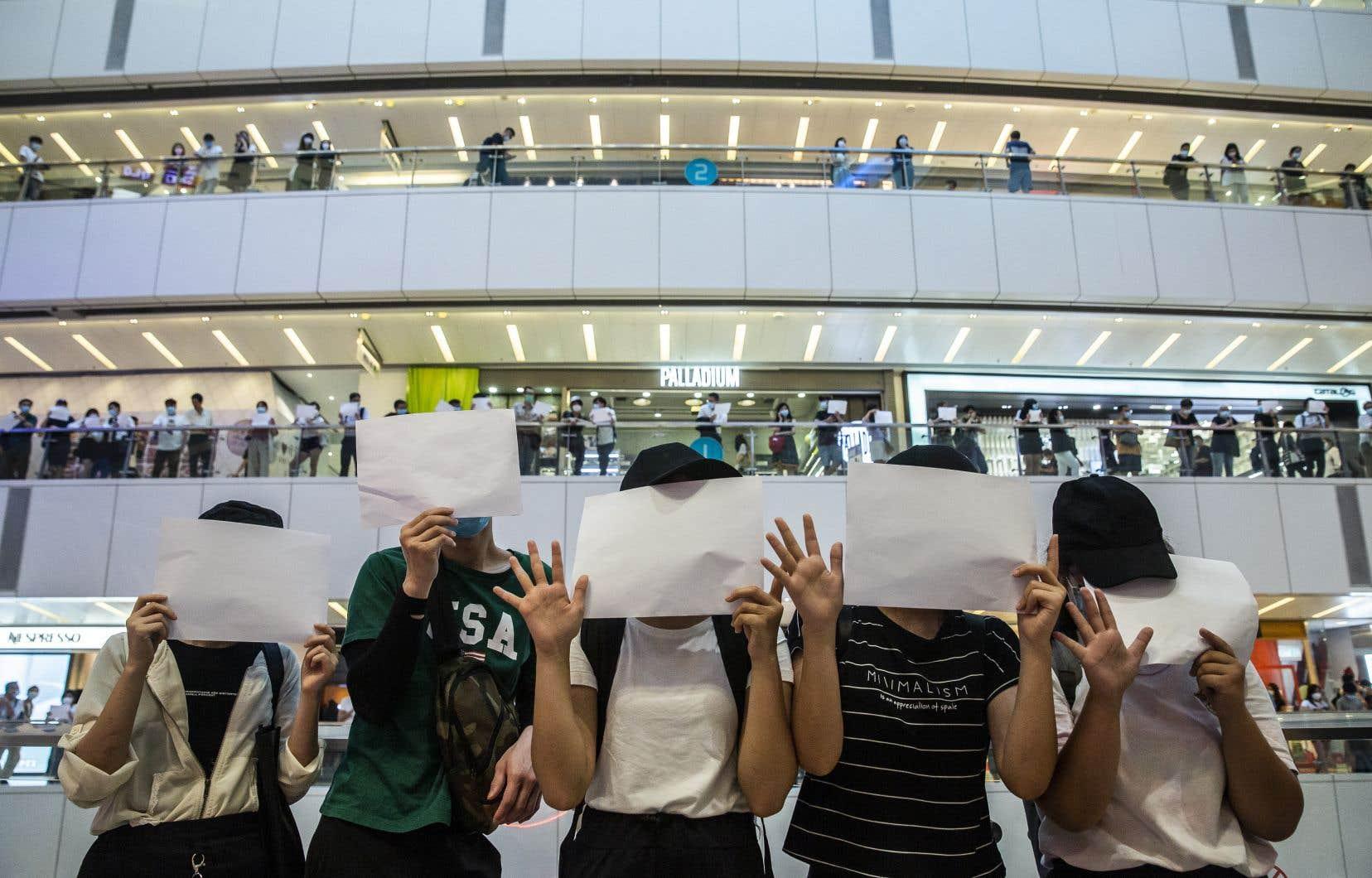 Les slogans pro-démocratie ou pour l'indépendance étant interdits par la loi de sécurité à Hong Kong, des manifestants ont fait preuve de créativité lundi en brandissant des feuilles de papier blanches en guise de protestation.