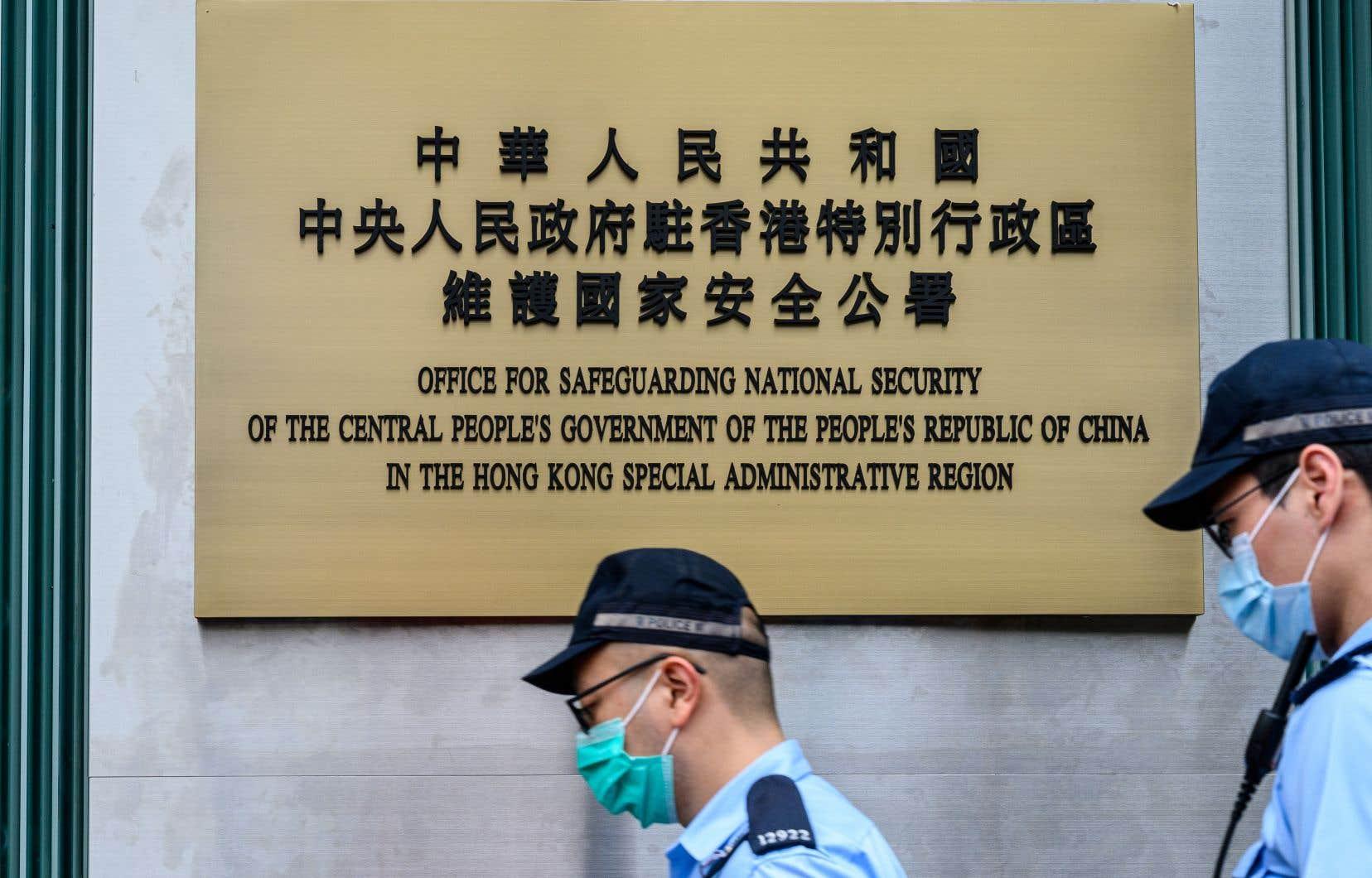 Des policiers passent devant une plaque à l'extérieur du Bureau de sauvegarde de la sécurité nationale du gouvernement populaire central, dans la région administrative spéciale de Hong Kong, après son inauguration officielle le 8 juillet 2020.