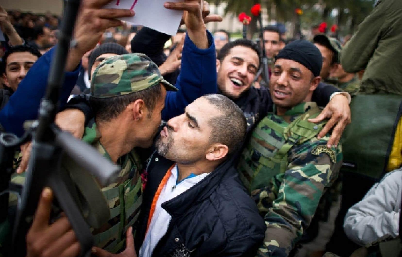 Un manifestant de Tunis protestant contre le parti fondé par le président déchu Ben Ali, le Rassemblement constitutionnel démocratique (RCD), embrasse un soldat. Les Tunisiens descendus dans la rue hier demandaient la démission des ministres de Ben Ali qui se sont joints au nouveau gouvernement d'union nationale. «RCD out!» criaient-ils. Pendant ce temps, le gouvernement de transition a tenu sa première rencontre, au cours de laquelle les ministres ont décrété un deuil national de trois jours et ont adopté un projet de loi d'amnistie générale.