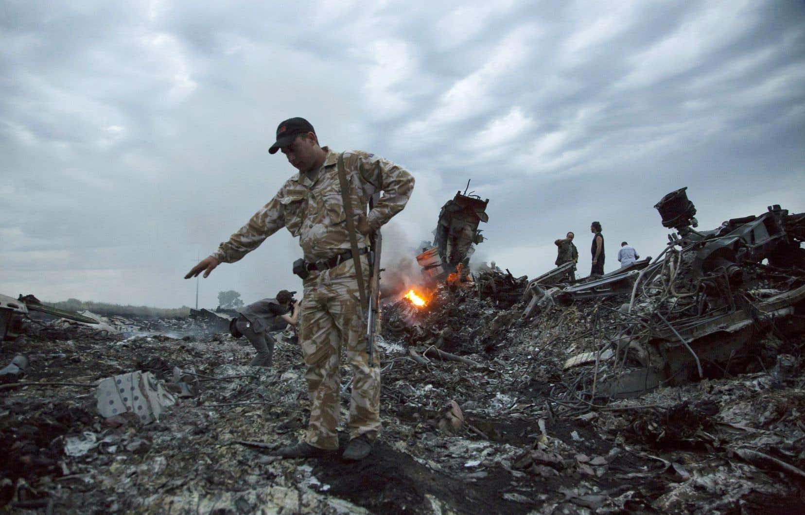 Des militaires parcourant les débris du vol MH17, abattu avec ses 298 passagers à bord, au-dessus de l'Ukraine