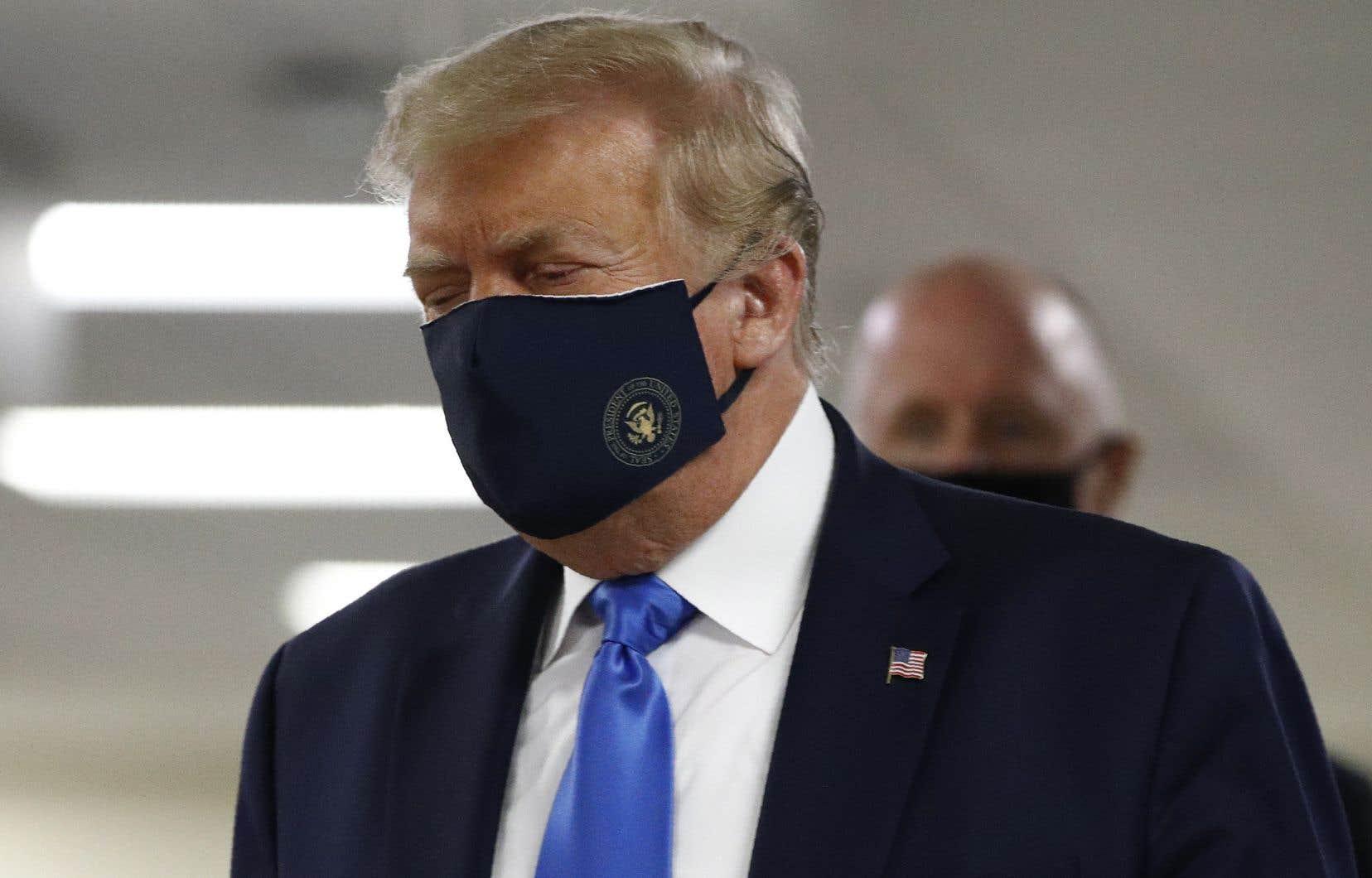 Le président des États-Unis, Donald Trump, portait un couvre-visage lors d'une visite dans un hôpital militaire en banlieue de Washington, samedi.