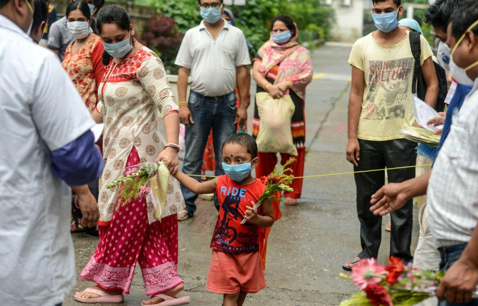 Des malades guéris du coronavirus recevaient le 1er juillet des fleurs à l'occasion de la journée nationale des médecins, à Siliguri, en Inde. Bien qu'ils répondent négativement aux tests, tous les patients ne sont cependant pas au bout de leurs peines.