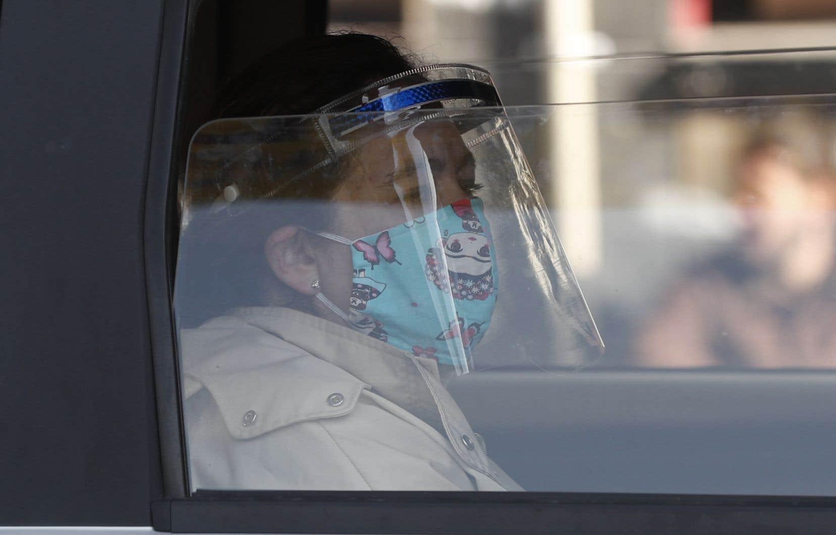 En Bolivie, une femme porte masque et visière dans l'autobus.