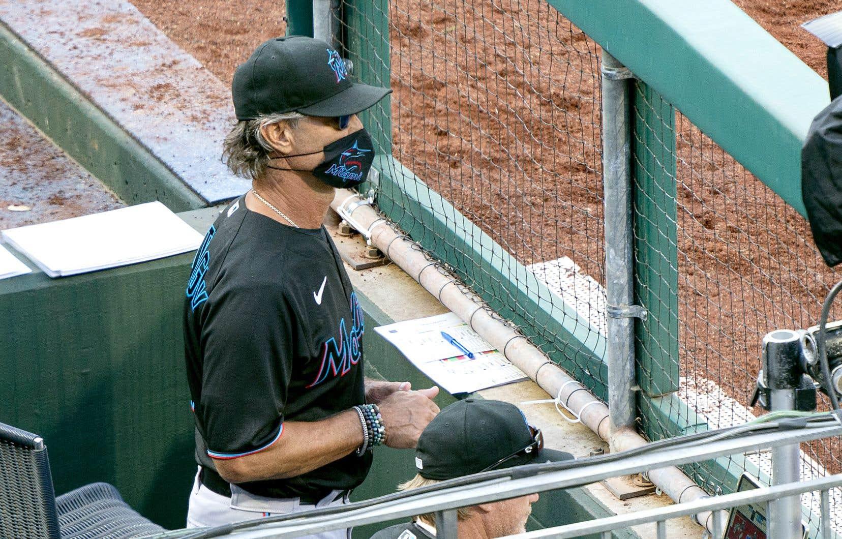 Le gérant des Marlins de Miami, Don Mattingly, porte un masque aux couleurs de son équipe dans l'abri des joueurs.