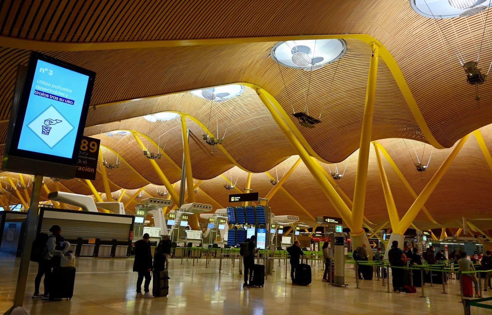 Des passagers font la file à l'aéroport Barajas Adolfo Suarez de Madrid, la ville où se situe le siège de l'Organisation mondiale du tourisme.