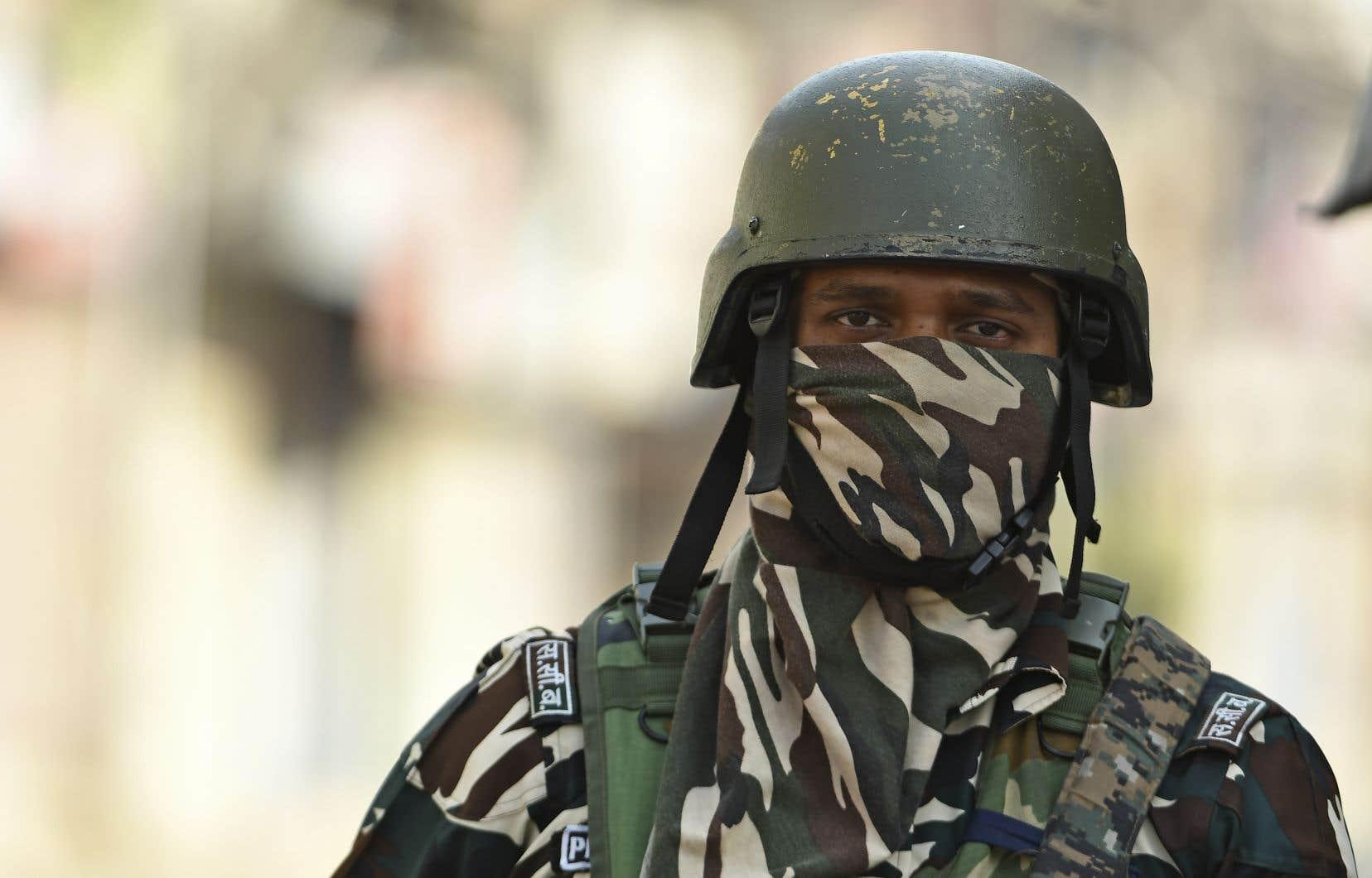 Un soldat paramilitaire monte la garde devant des magasins fermés lors d'un couvre-feu à Srinagar le 4 août 2020.