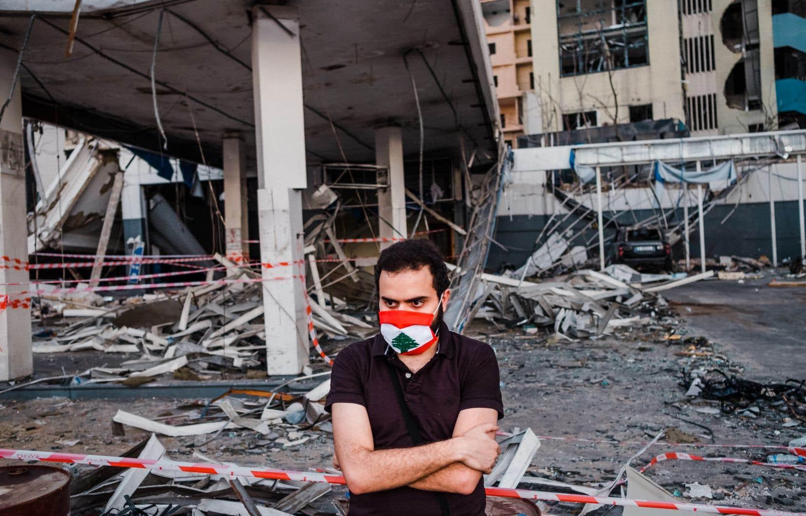 Un homme constatait dimanche les dégâts dans le quartier voisin du port de Beyrouth.
