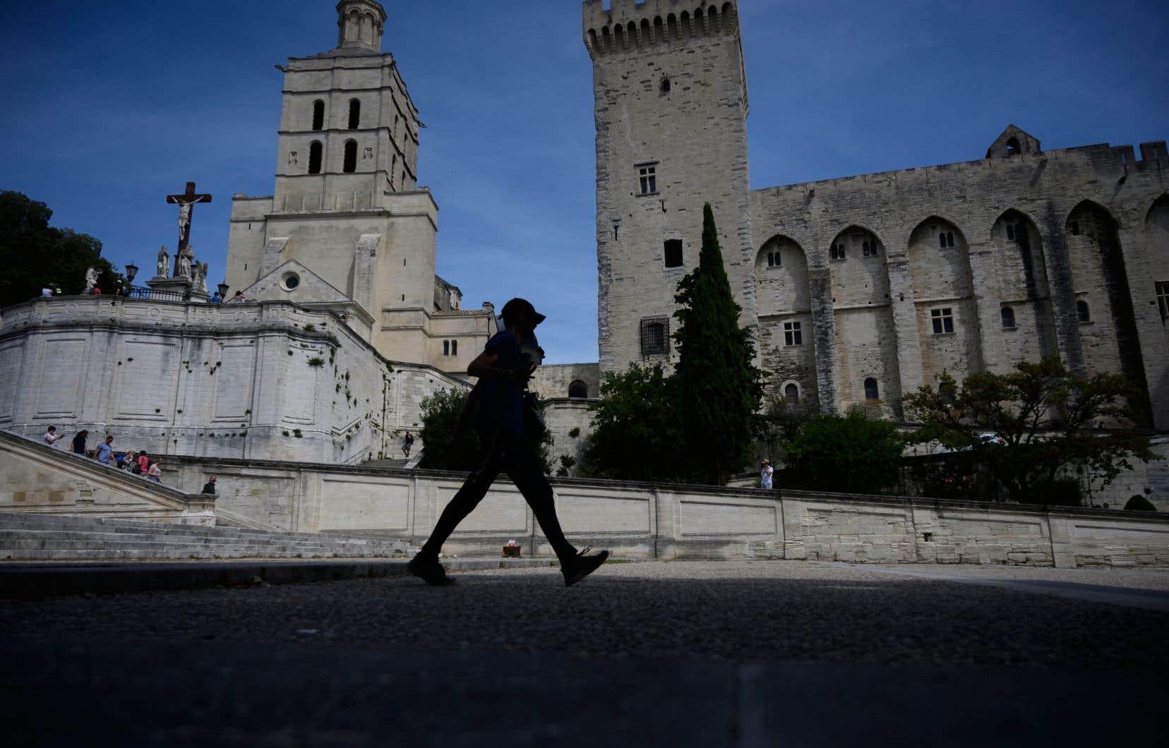 Une personne marche près du Palais des Papes, à Avignon. La ville a dû changer son offre touristique pour compenser les effets de la pandémie.