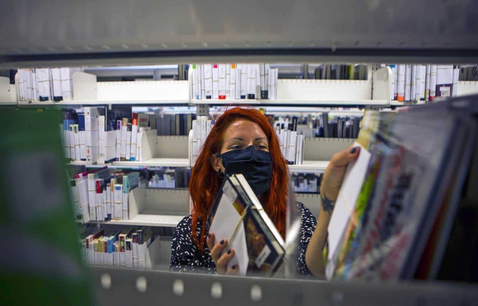 Une employée de la Grande Bibliothèque portait un masque lors de la réouverture de l'établissement, début juillet. Selon une nouvelle étude, le couvre-visage ne ferait pas que réduire la propagation de la COVID-19.