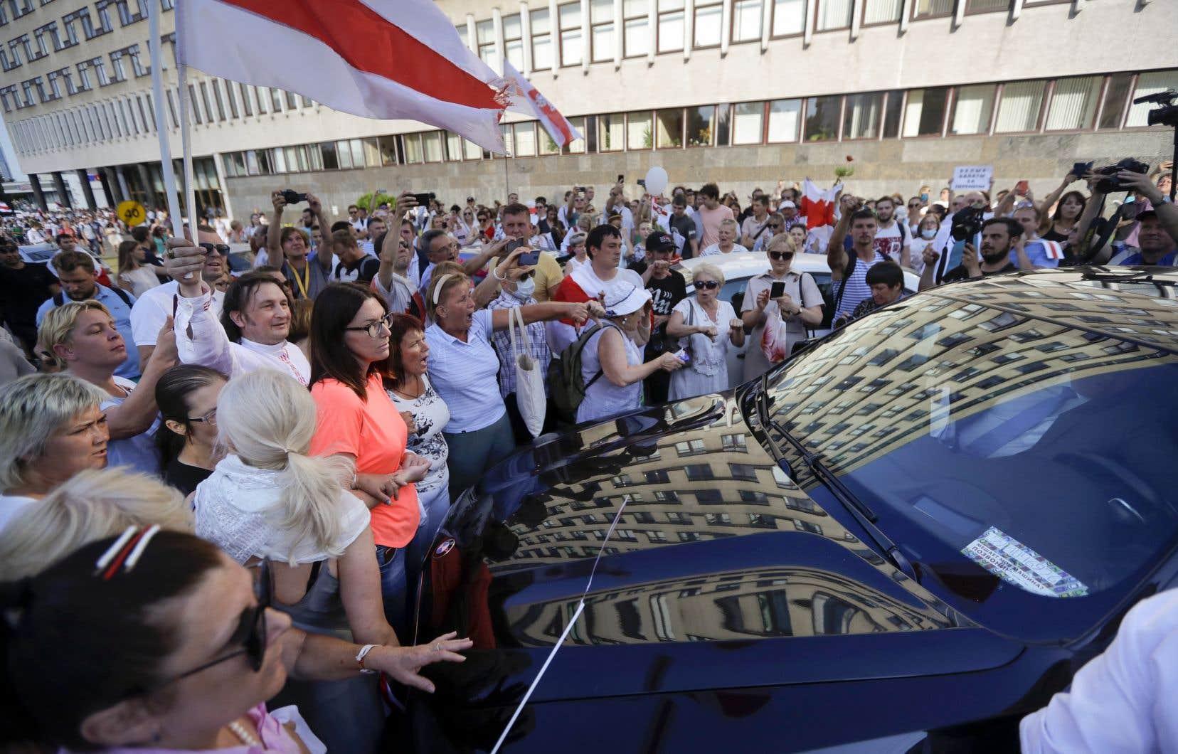 Alors que, depuis quelques jours, les défilés sont toujours joyeux et pacifiques, les Biélorusses semblent perdre patience devant les officiels du régime. Sur la photo, des manifestants ont bloqué, lundi à Minsk, une voiture conduisant le ministre de la santé, Uladzimir Karanik.