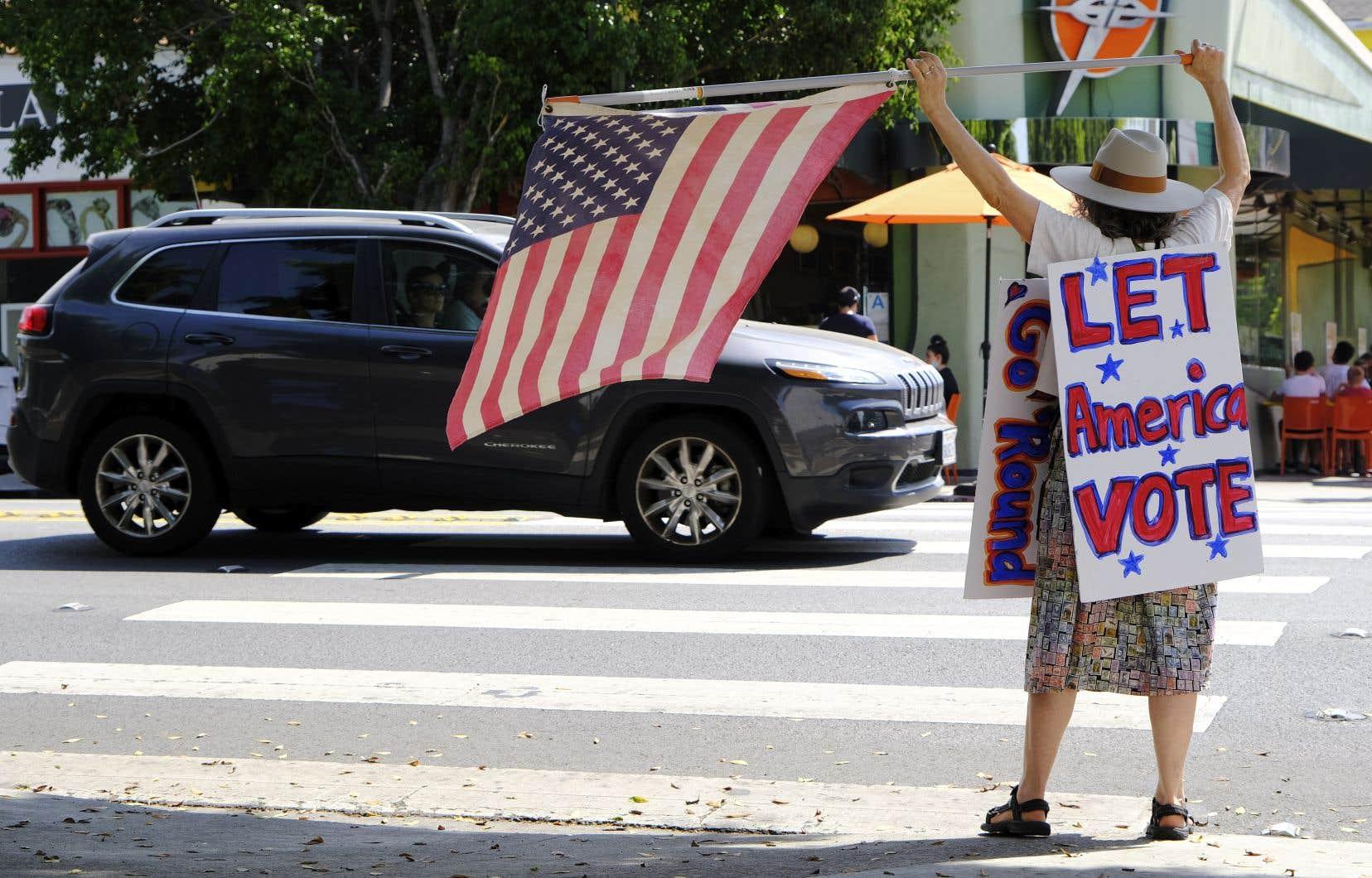 Une femme manifeste devant un bureau du service postal américain, à Los Angeles.