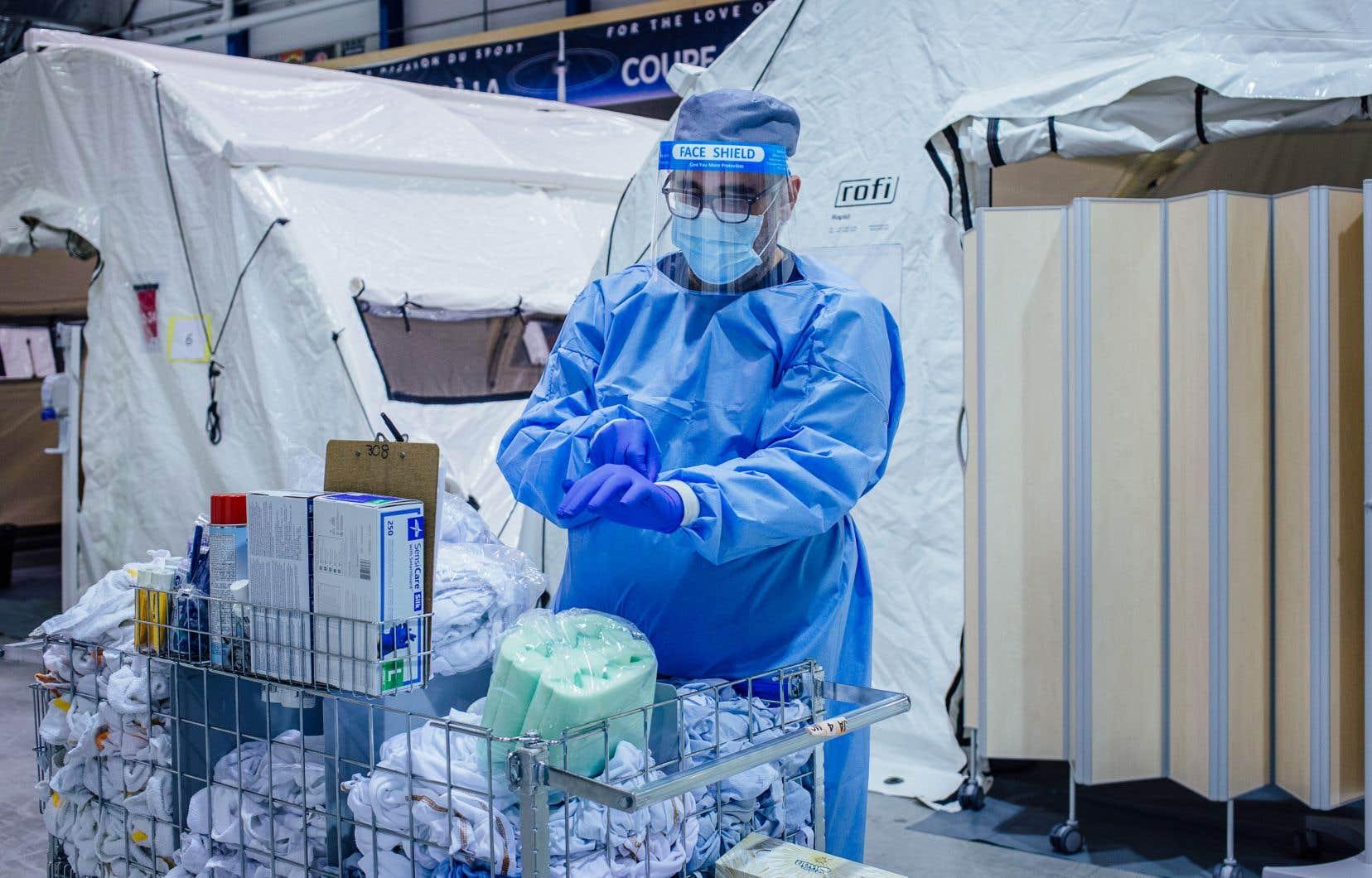 Un membre du personnel soignant enfile des gants pour traiter des patients à l'hôpital de campagne installé dans l'aréna Jacques-Lemaire de LaSalle au printemps.