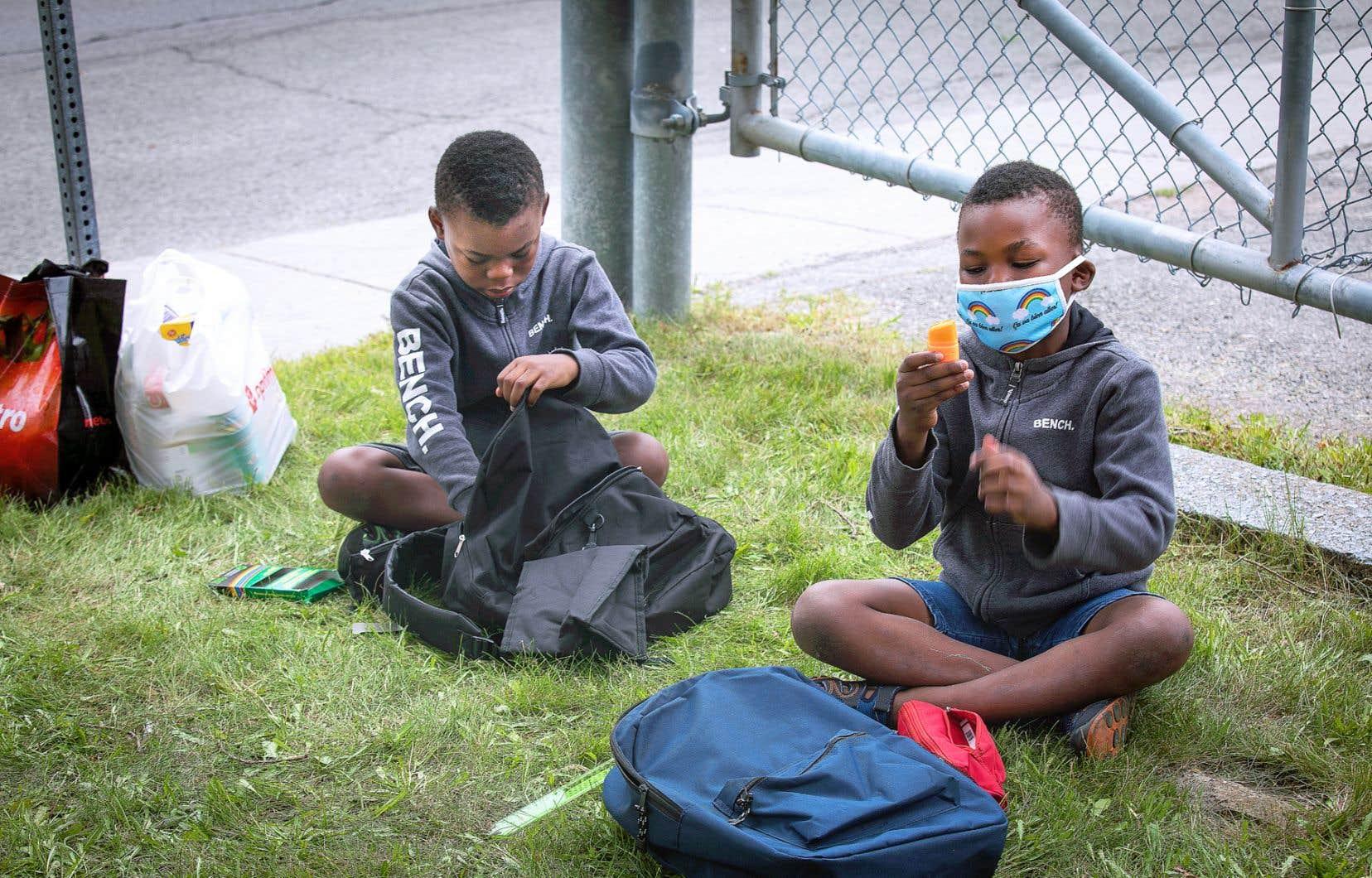 Les jumeaux Divinshy et Vinshy, 7 ans, découvrent avec joie le contenu de leur sac d'école qui leur a été offert.