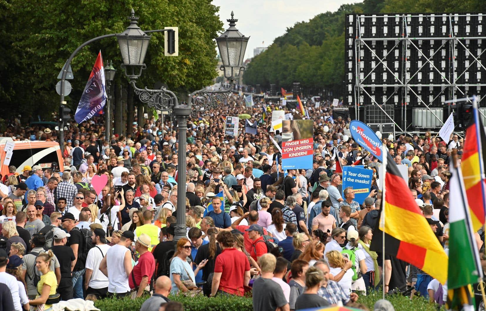 Les drapeaux de la paix arc-en-ciel et de l'Allemagne se côtoyaient à Berlin au-dessus d'une foule très mélangée, de toutes classes d'âge, comprenant des familles avec des enfants en bas âge.