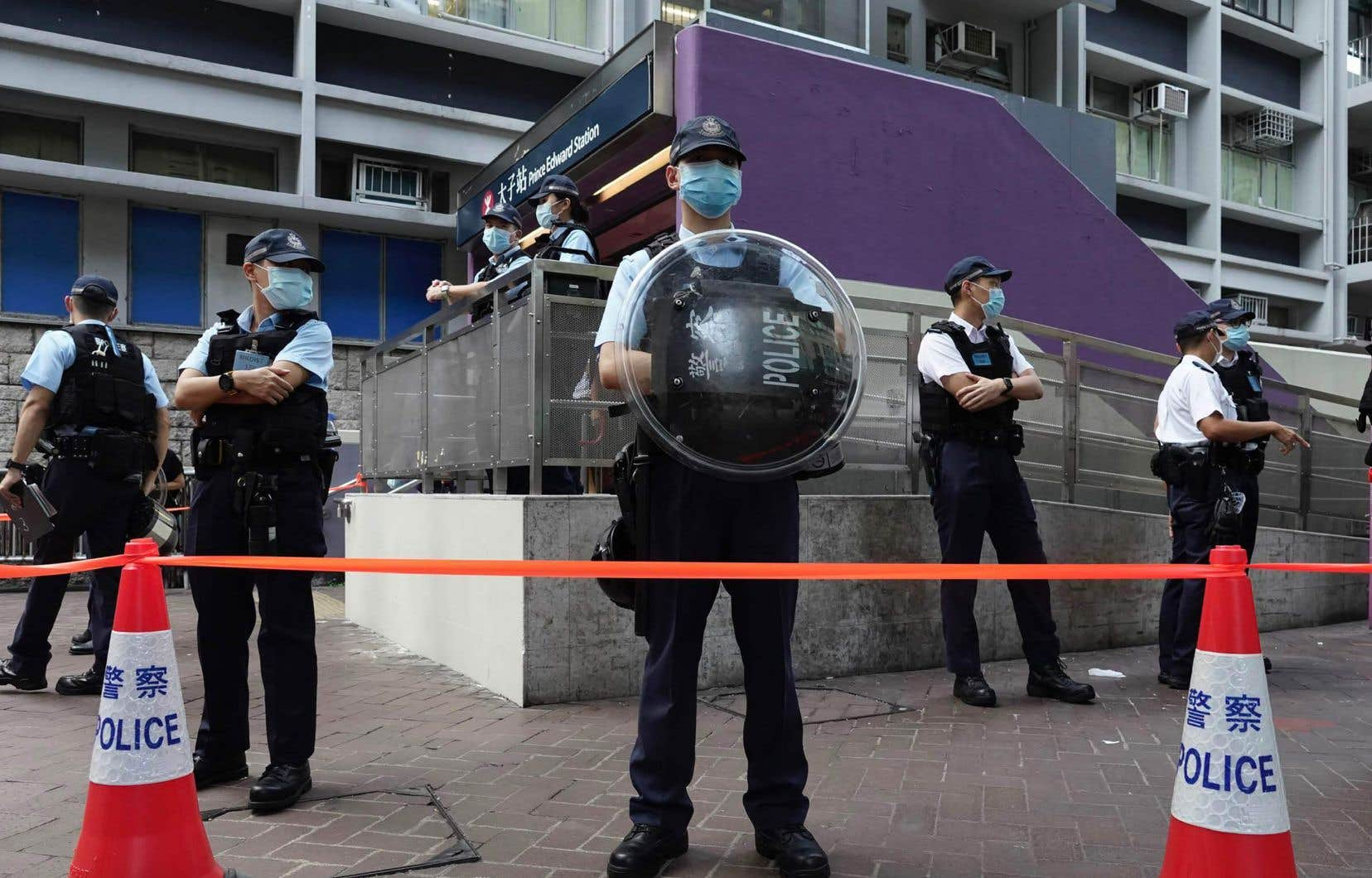 Des policiers montent la garde de la station de métro Prince Edward, où des manifestants ont été violemment battus par des policiers il y a un an, le 31 août 2019.