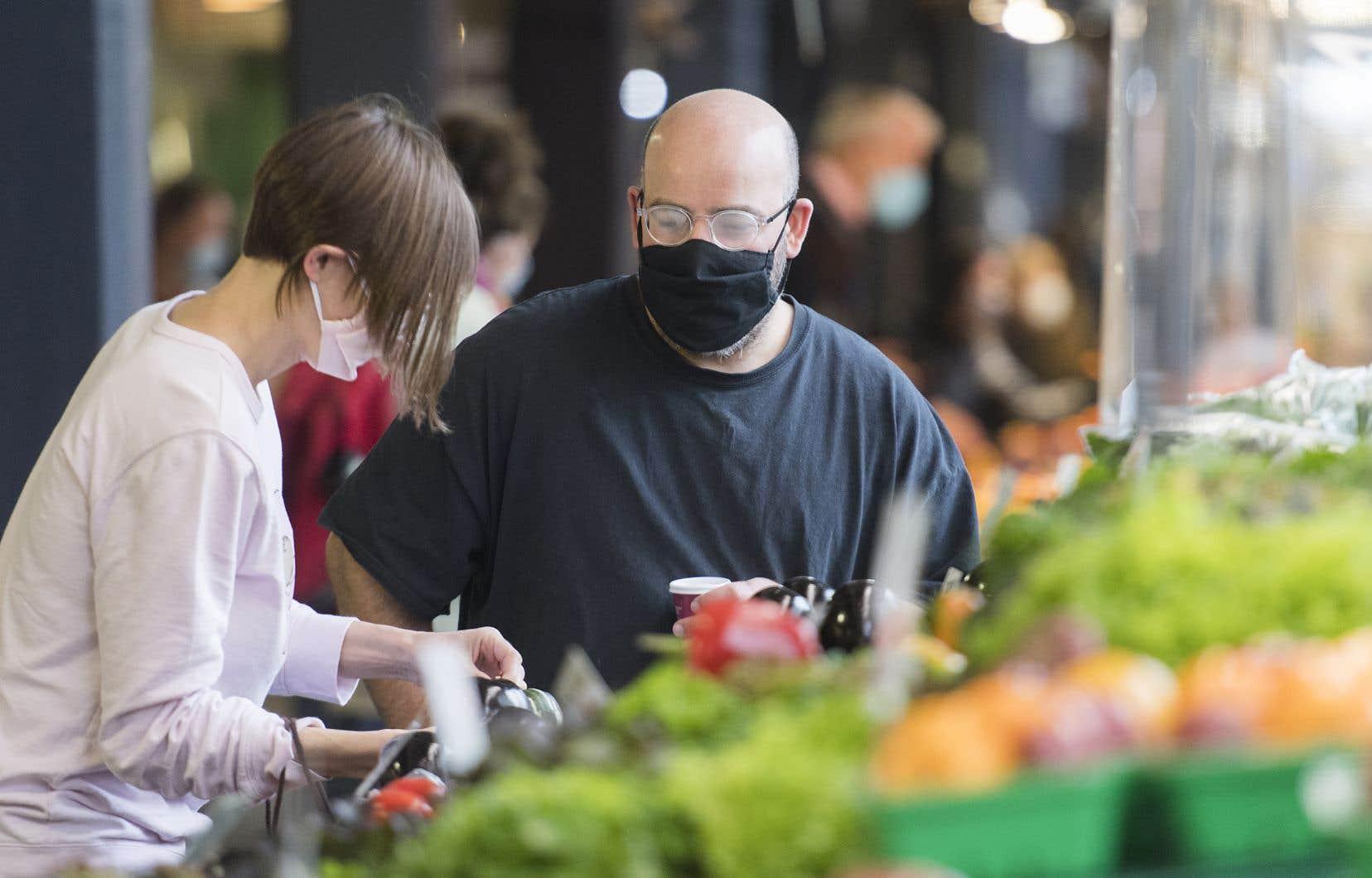 Des clients portant un couvre-visage faisaient leurs emplettes dans un marché public montréalais, dimanche. Le nombre de cas de COVID-19 a bondi ce week-end.