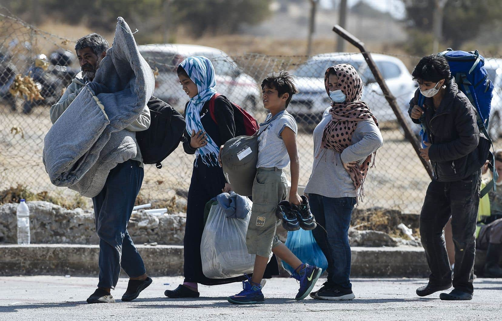 Plusieurs exilés, dont bon nombre de familles, se présentent bon gré mal gré dans le nouveau camp temporaire dressé à quelques encablures des ruines de Moria.