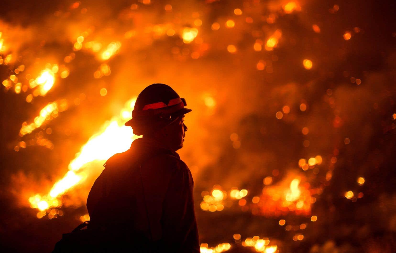 Un pompier observe les flammes lécher les flancs des collines près du parc Monrovia, non loin de Los Angeles. Si à San Francisco les habitants ont pu profiter de la journée d'hier pour ouvrir les fenêtres et aérer leurs maisons, cela ne signifie pas pour autant que la situation est maîtrisée partout: les incendies continuent de faire rage.