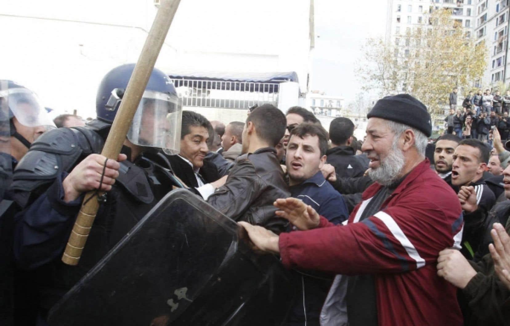 Un policier algérien brandissait une matraque de bois alors que la foule manifestait, samedi à Alger. Pendant plus de cinq heures qu'a duré le rassemblement, les manifestants ont dû lutter pour éviter d'être dispersés ou divisés en plusieurs groupes plus faciles à repousser par les forces anti-émeutes.