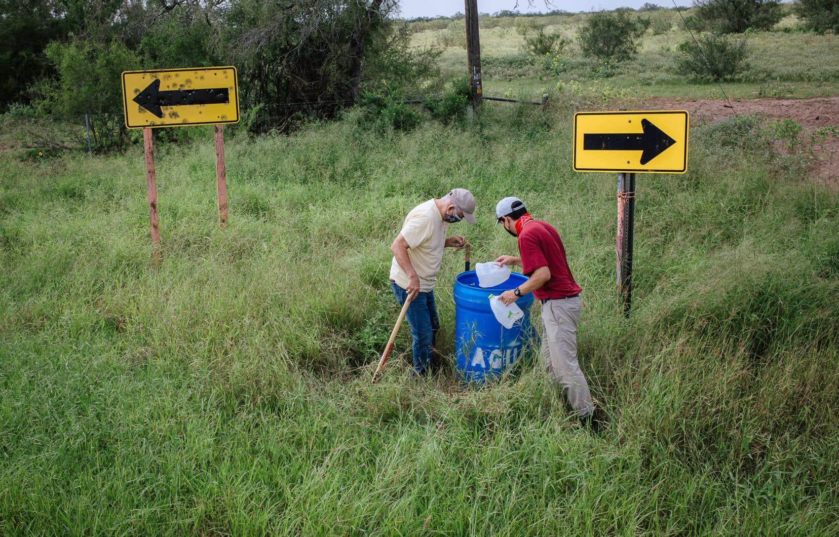 Eddie Canales et le bénévole Matthew Flores inspectent une station d'eau lors d'une tournée de réapprovisionnement des installations dans le comté de Brooks.