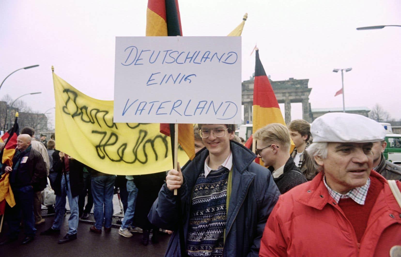 Un jeune allemand tient une banderole sur laquelle on lit «Allemagne patrie unie», lors d'une manifestation devant la porte de Brandebourg, Berlin est, le 22 décembre 1989.