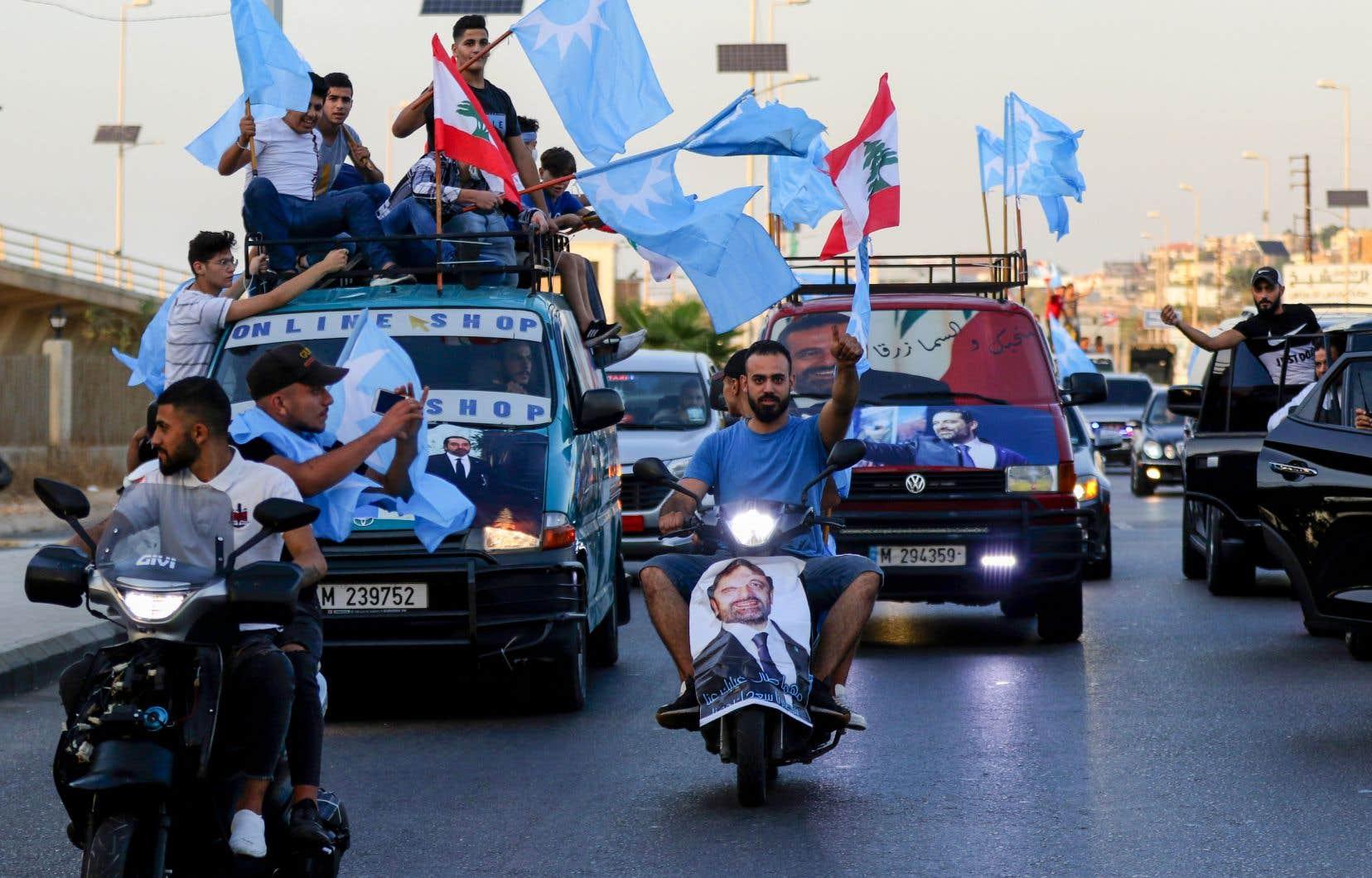 Des partisans de Saad Hariri agitent le drapeau de son parti et le drapeau national libanais lors d'un défilé pour célébrer sa mission de former un nouveau gouvernement.