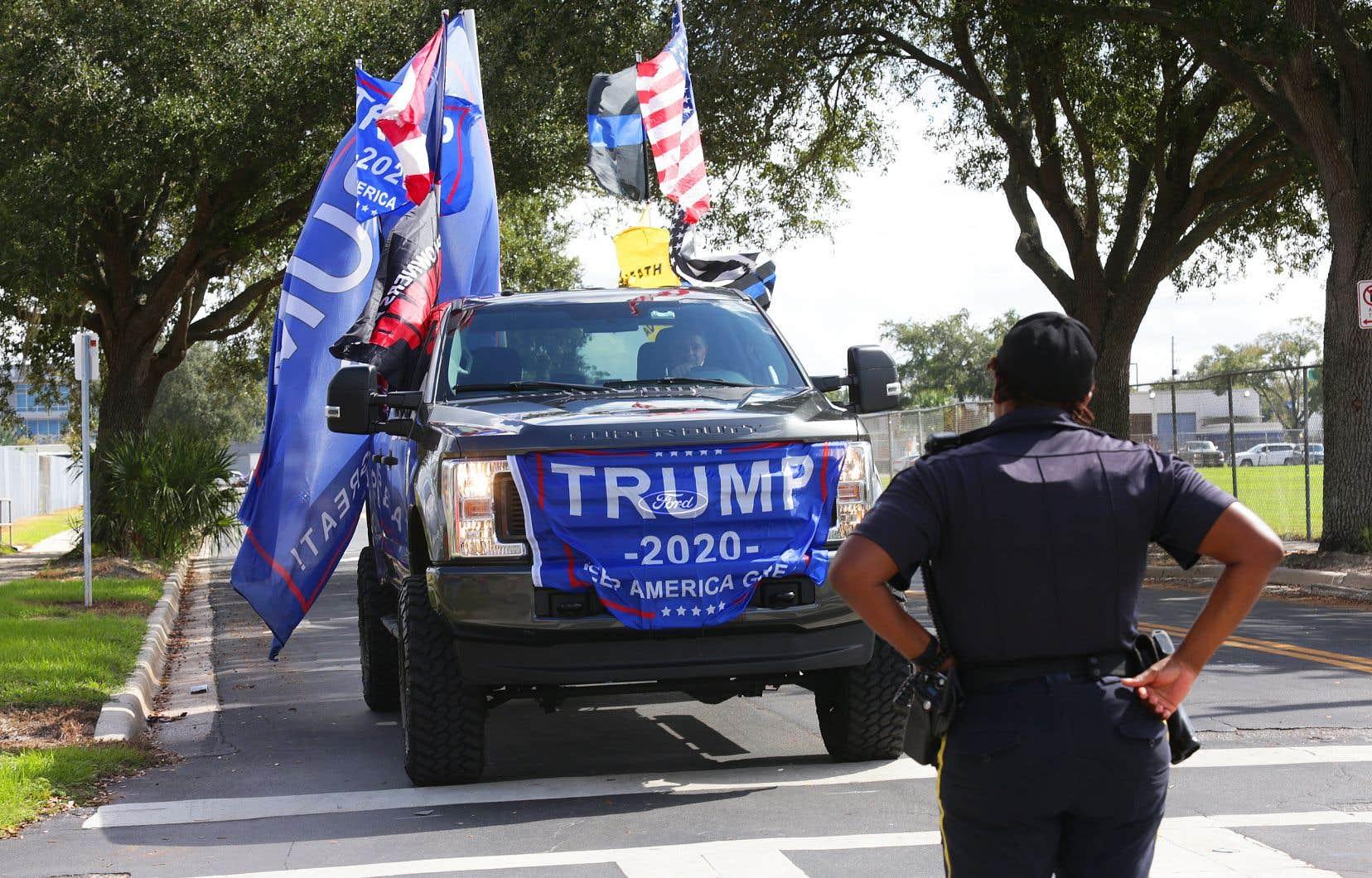 Une policière a demandé à un partisan de Trump à bord d'une camionnette de faire demi-tour, en marge du discours de l'ancien président Barack Obama, mardi, dans un stade d'Orlando, en Floride.