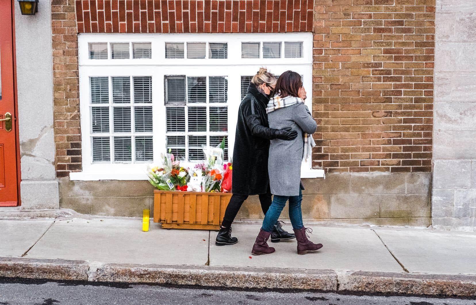 Deux femmes se sont recueillies dimanche après devant la résidence de Suzanne Clermont, l'une des victimes.