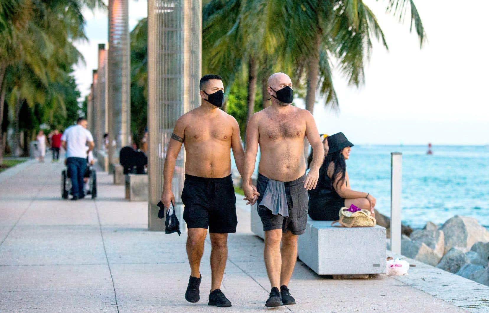 Torses nus, Simone Onnis (à gauche) et Derek Yarbrough (à droite) détonnent avec leurs masques pendant leur promenade sous les palmiers du South Pointe Park Pier. «Trois membres de ma famille ont eu la COVID-19», explique Derek Yarbrough. «Je trouve ça stupide que ça devienne un enjeu politique.»