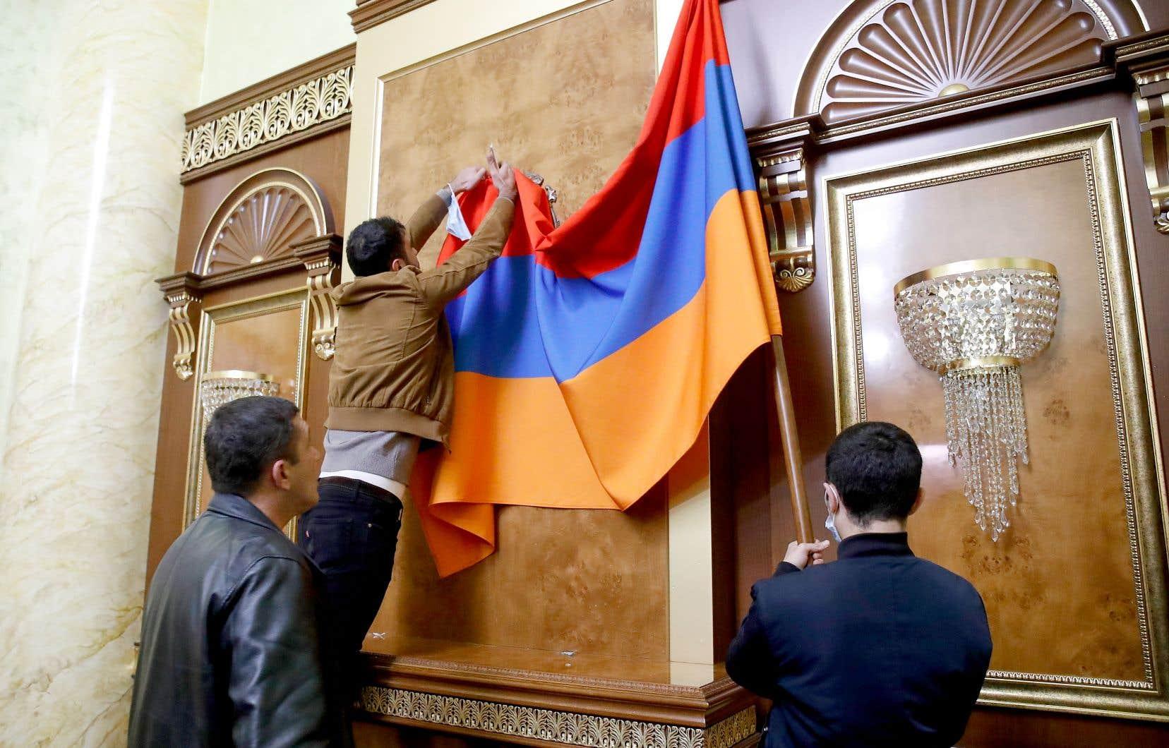 Des gens installaient un drapeau arménien au siège du gouvernement à Erevan, lundi, protestant contre l'entente qui met fin au conflit dans le Haut-Karabakh.