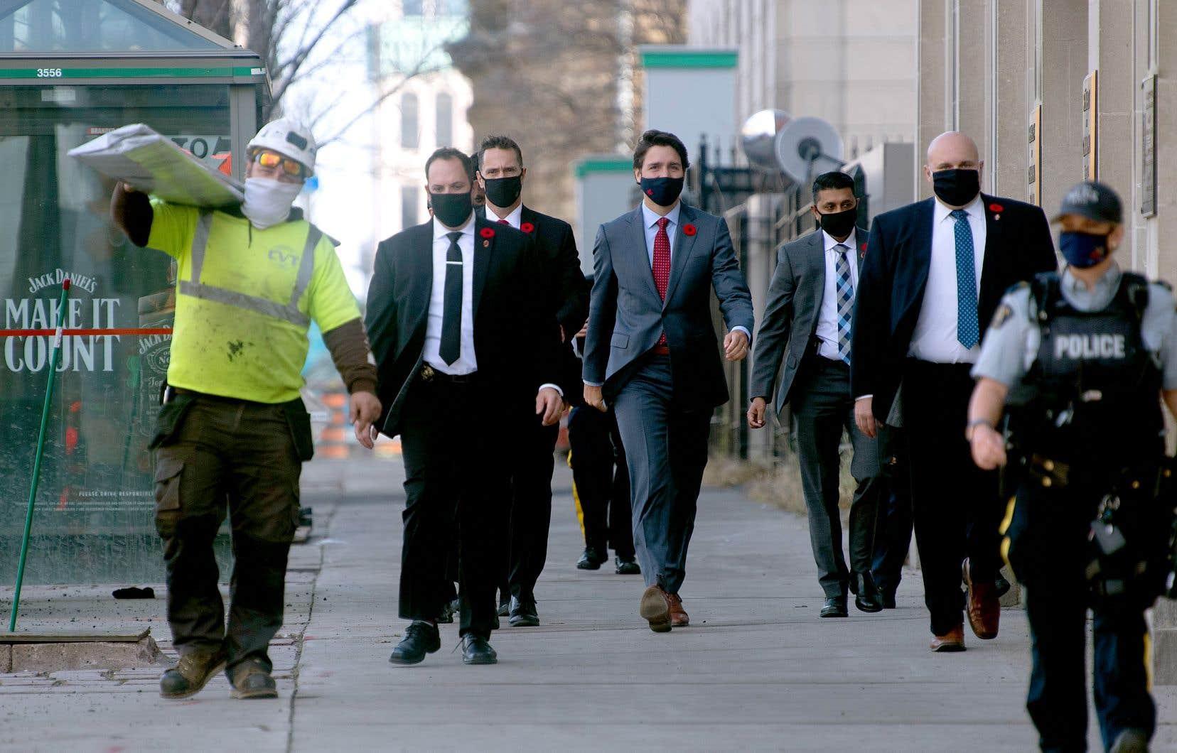 Le premier ministre Justin Trudeau et des membres de son service de sécurité marchent en direction du Centre des conférences à Ottawa. M. Trudeau a laissé entendre, mardi, qu'il cherchait des solutions de remplacement à la détention en matière d'immigration.
