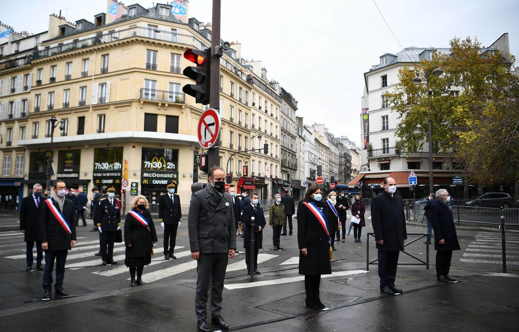 Accompagné notamment de la maire de Paris Anne Hidalgo (devant au centre), le premier ministre Jean Castex (troisième à partir de la gauche) s'est rendu dans la matinée en différents lieux de Paris, cibles des commandos téléguidés par le groupe État islamiqueil y a cinq ans.