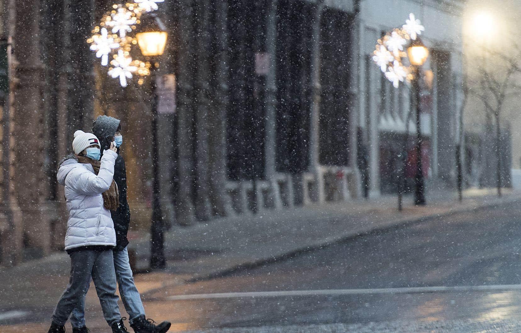 Des passants circulent dans les rues de Montréal alors que la neige tombe sur la ville.