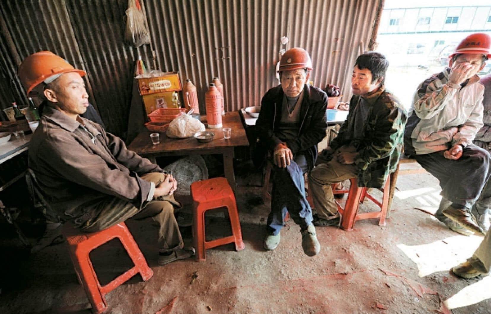 Des travailleurs migrants prennent une pause apr&egrave;s le d&icirc;ner avant de reprendre le boulot.<br />