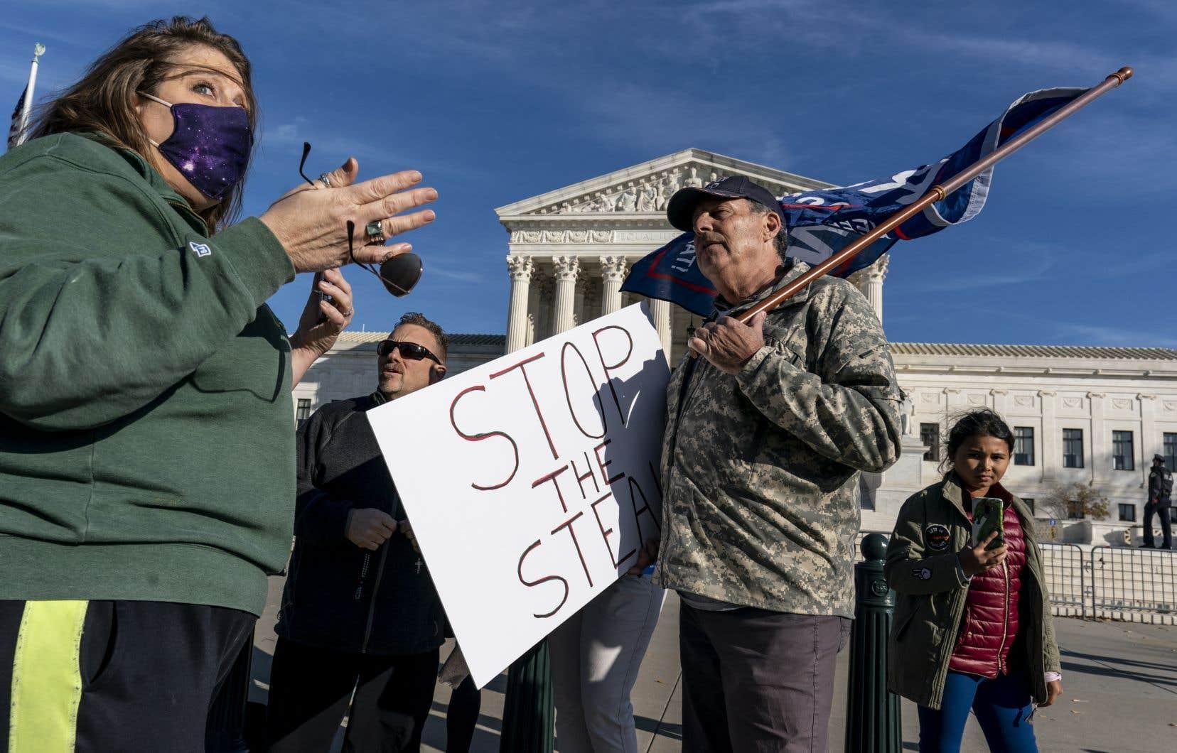 Quelques partisans de Donald Trump étaient présents vendredi devant le bâtiment de la Cour suprême, à Washington. Ils discutent avec des opposants au président sortant.