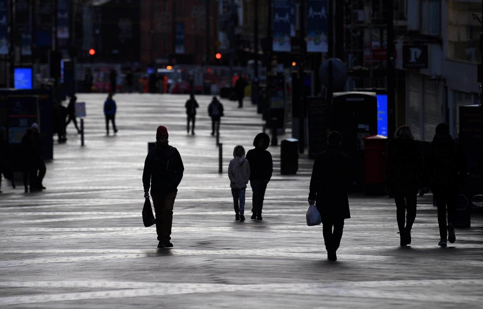 Des gens passent devant des boutiques fermées à Leeds, en Angleterre. Le pays est revenu à un long et dur troisième confinement.
