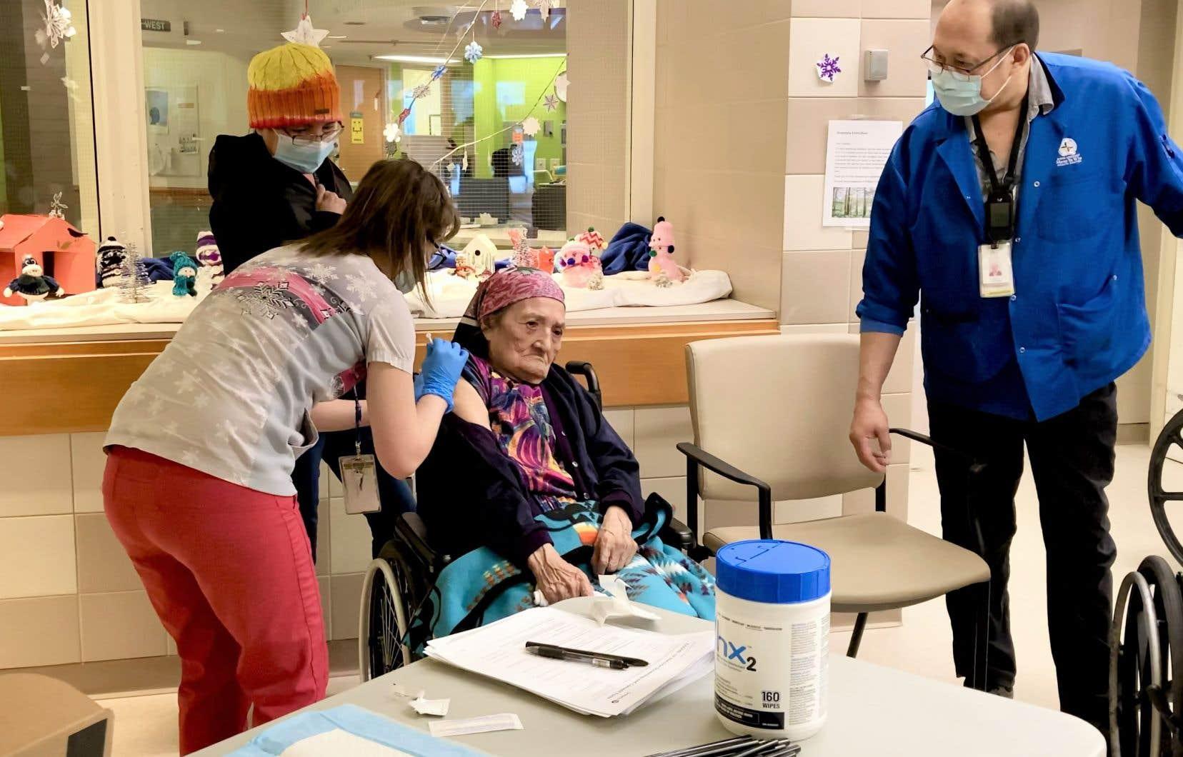 Eunice Fiddler reçoit une dose de vaccin contre la COVID-19 sous l'oeil de sa fille Margaret Beardy et d'un interprète, Tom Chapman, àSioux Lookout, en Ontario.