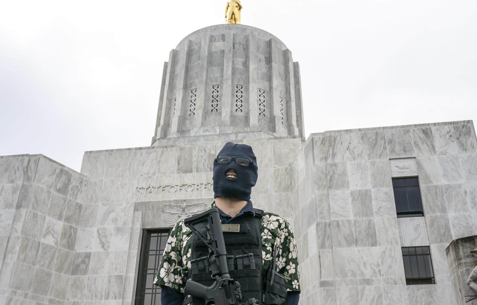 Un manifestant armé devant le Capitole d'État de l'Oregon, où la rentrée parlementaire a été retardée en raison des violences potentielles.