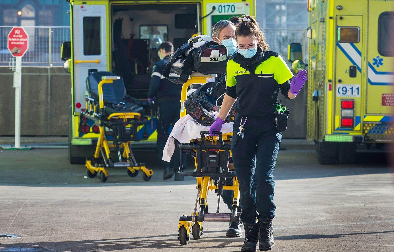 Une ambulancière masquée conduit un patient sur une civière à l'hôpital.